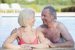 Couple in outdoor pool smiling. Couple in outdoor swimming pool smiling at each other Royalty Free Stock Image