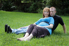Couple Outdoors. A husband and wife sitting in the grass.  The wife is approximately 26 weeks pregnant Stock Images