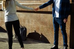 Couple outdoors against the wall and backpacks, farewell, parting, end. Open hands, open hands, fingers stock photo