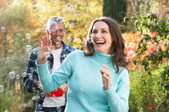 Couple Outdoors With Bubble Machine Royalty Free Stock Photos