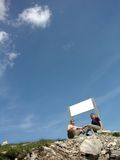 Couple, outdoors,clouds on blue sky, white tablet Royalty Free Stock Photos