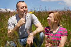 Couple outdoors with electric cigarette. Couple in a meadow with electric cigarette royalty free stock images