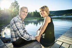 Couple outdoors by lake having good time Stock Photography