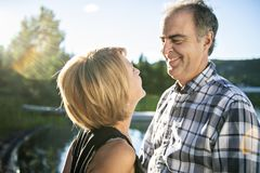 Couple outdoors by lake having good time Stock Images