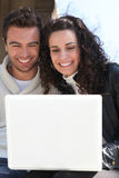 Couple outdoors with laptop. Smiling couple outdoors with a laptop stock image