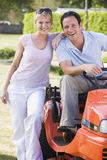 Couple outdoors with lawnmower smiling Stock Image