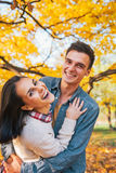 Couple outdoors in park in autumn having fun time Stock Photos