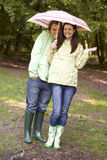 Couple outdoors in rain with umbrella smiling Royalty Free Stock Photo