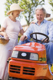 Couple outdoors with tools and lawnmower smiling Royalty Free Stock Images