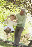 Couple outdoors with tree swing smiling Stock Images