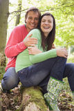 Couple outdoors in woods sitting on log smiling Royalty Free Stock Image