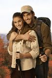 Couple outing in autumn countryside. Happy young couple outing in autumn countryside, embracing, holding trekking poles Stock Images