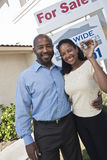 Couple Outside New Home. Portrait of multiethnic happy couple with house keys standing outside new home Royalty Free Stock Images