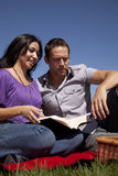 Couple outside reading book Royalty Free Stock Images