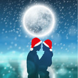 Couple over background with moon and snowflakes Stock Photography