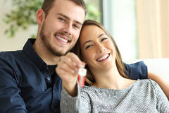 Couple of owners showing house keys. Happy couple of owners showing house keys to the camera sitting on a sofa in the living room at home Royalty Free Stock Photos