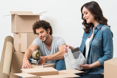 Couple Packing Cardboard Box. Portrait Of Happy Young Couple Packing Cardboard Boxes Royalty Free Stock Photography