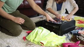 Couple packing clothes into suitcase for journey stock video footage