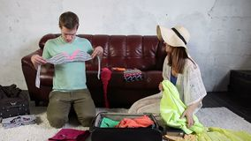 Couple packing for holiday trip and having fun stock footage