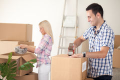 Couple packing moving boxes. Young couple packing moving boxes, ready for move out Royalty Free Stock Photos
