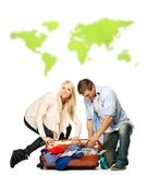 Couple packing suitcase against world map Stock Image