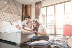 Couple packing suitcase on floor in room use tablet for search travel trip online pay by credit card. Happy couple packing suitcase on floor in room use tablet stock photo