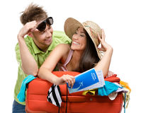 Couple packs suitcase with clothing for travel. Isolated on white. Concept of romantic vacations and lovely honeymoon Royalty Free Stock Photo