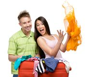 Couple packs suitcase with clothing for trip Stock Photo