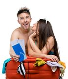Couple packs suitcase and tries on clothing for traveling Royalty Free Stock Image