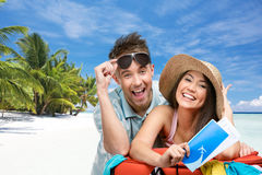Couple packs up suitcase with clothing for honeymoon trip. Tropical beach background. Concept of romantic vacations and lovely honeymoon Stock Image