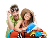 Couple packs up suitcase with clothing for trip. Couple packs up suitcase with clothing for departure, isolated on white. Concept of romantic vacations and Royalty Free Stock Photo