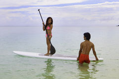 Couple with paddle board. Hawaiian beachboy teaches young woman to paddleboard Stock Images