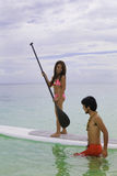 Couple with paddle board. Hawaiian beachboy teaches young woman to paddleboard Stock Image