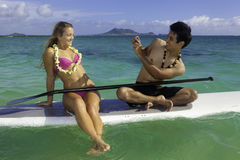 Couple on paddle board photographing Stock Photos