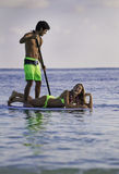 Couple on a paddleboard. Young couple on a paddleboard in a hawaii lagoon Royalty Free Stock Image