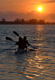 Couple paddling a canoe. To cross the river when the sunset Royalty Free Stock Photo