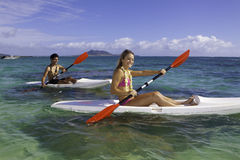 Couple paddling surfskis Stock Photo