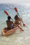Couple paddling their kayak royalty free stock photography