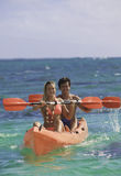 Couple paddling their kayak Royalty Free Stock Image