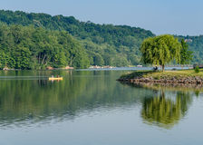 Couple paddling in yellow canoe on tree lined lake Royalty Free Stock Image