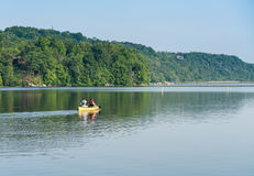 Couple paddling in yellow canoe on tree lined lake Royalty Free Stock Photos