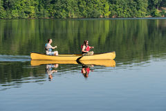 Couple paddling in yellow canoe on tree lined lake Stock Photos