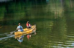 Couple paddling in yellow canoe on tree lined lake Stock Image