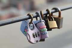 Couple padlocks are locked on rail with blurred city background, everlasting friendship symbol or forever love concept Royalty Free Stock Images