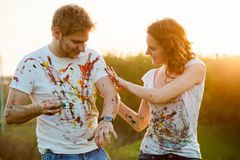 Couple paint on each other stock photo