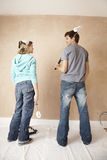 Couple With Paint Roller Looking At Each Other Against Wall Royalty Free Stock Photo