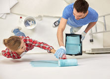 Couple with paint roller painting wall at home stock photos