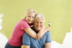 Couple with paintbrushes. Portrait of smiling adult couple sitting in front of half-painted wall with paintbrushes Royalty Free Stock Photography