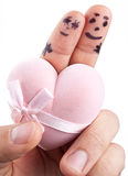 Couple painted on man's fingers. Couple painted on man's fingers and gift box in the form of heart stock photography