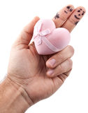 Couple painted on man's fingers and gift box in the hand. Couple painted on man's fingers and gift box in the form of heart stock image